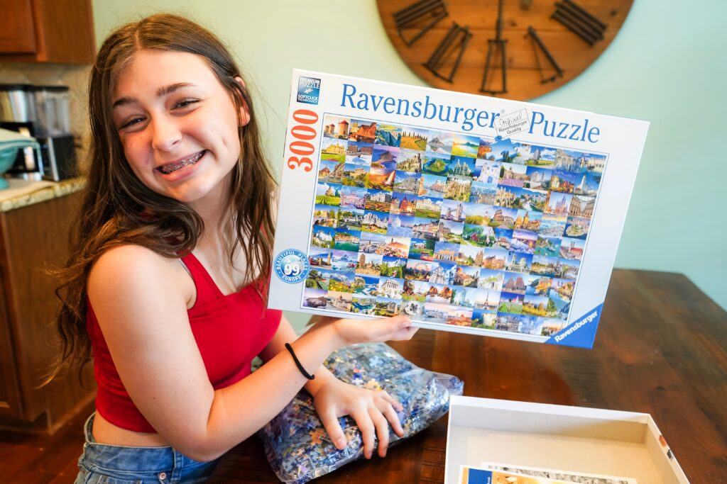 Teen Girl holds up giant 3000 piece jigsaw puzzle. Now is the perfect time to try a challenging puzzle that will take at least a couple of days to complete. Set it up on your dining room table or find an empty spot where you can all work together. - Safe Summer Bucket List – 100 Ways to Have Fun This Summer While Social Distancing