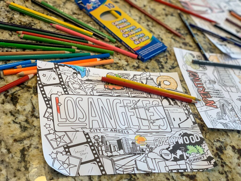 Coloring book page surrounded by colored pancils. There is something calming about coloring at any age. -Safe Summer Bucket List – 100 Ways to Have Fun This Summer While Social Distancing. Grab a coloring book and some crayons or fancy blending markers and enjoy quiet time coloring.