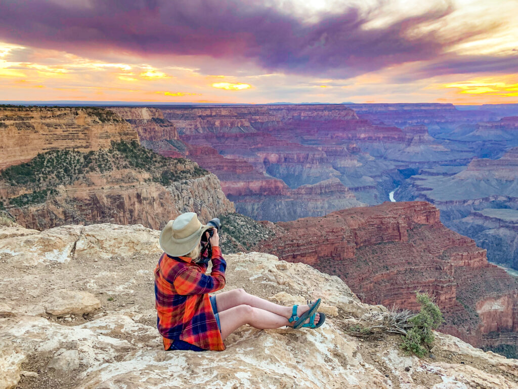 Woman looks out at sunset over Grand Canyon from Hopi Point. Virtually touring a national park is a fun way to pass the time and scout places for a future in-person exploration.