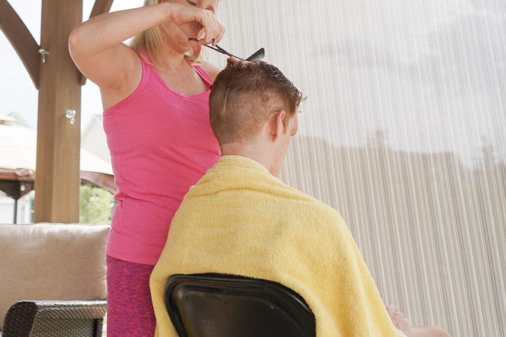 Teenage boy gets hair cut on patio. We've learned that the patio is a great place for hair cuts and getting creative like using leaf blower can add an extra element of fun. You can find some great hair cut tutorials on you tube.