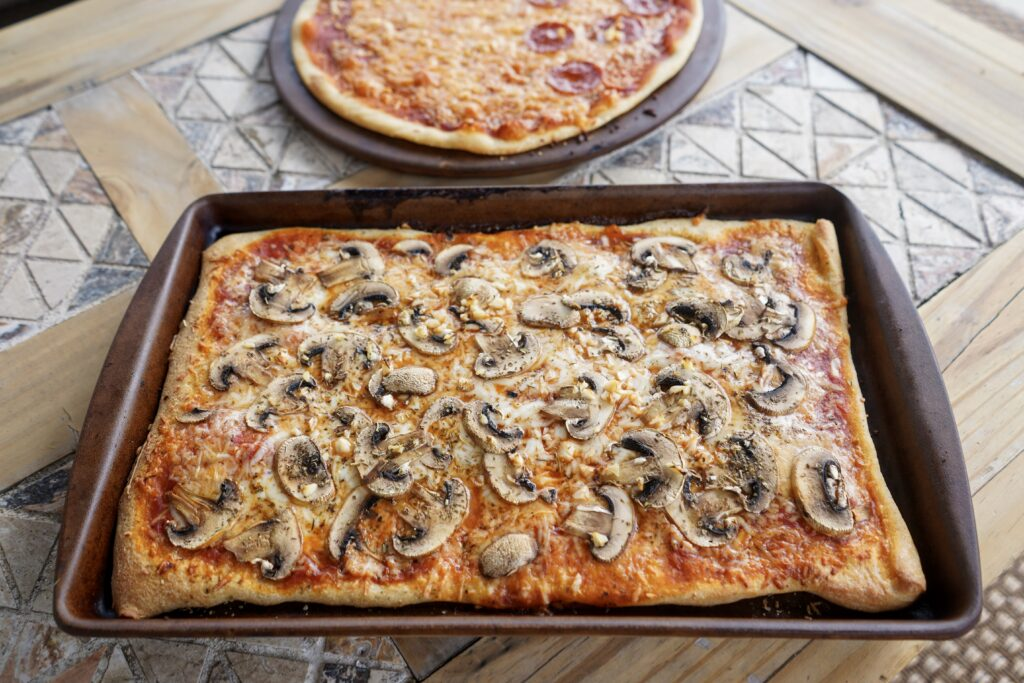 Pan of homemade pizza. Skip the pizza delivery and make your own from scratch instead including the dough! Everyone can take a turn tossing and putting on own tomato sauce, cheese, and toppings.