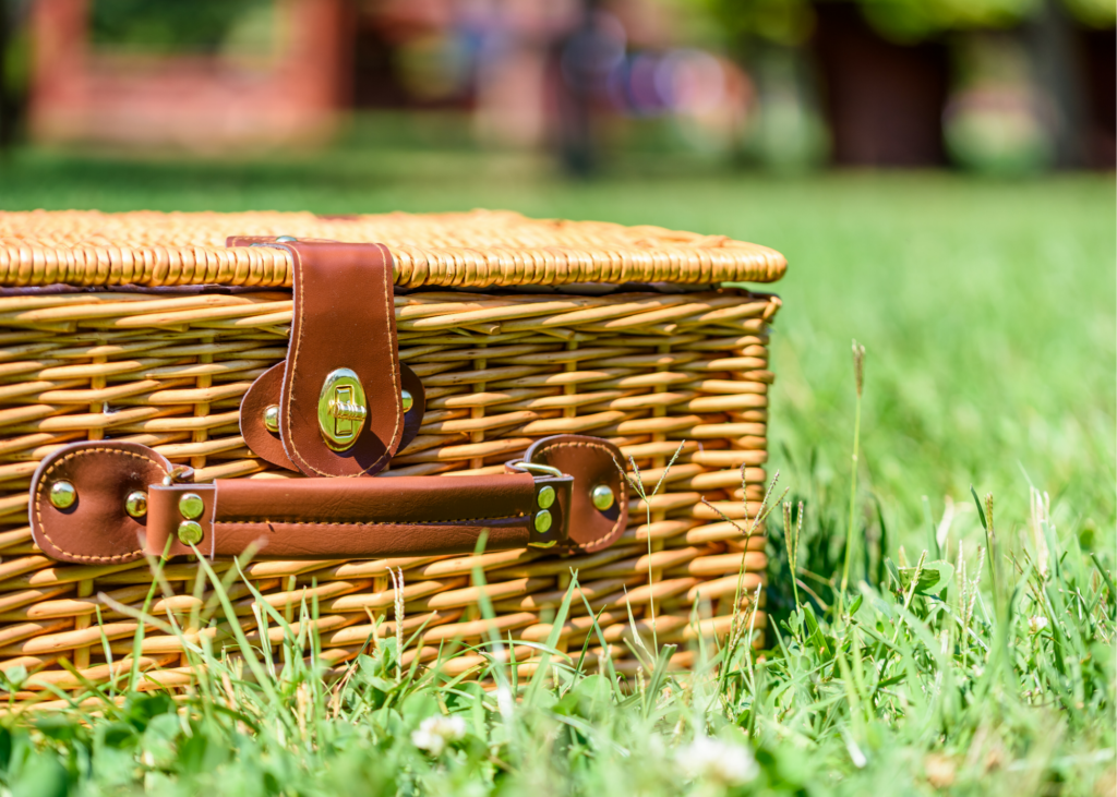 Image of a wicker picnic basket in the grass. Complete with a blanket and basket, enjoy a picnic in your backyard, or a secluded spot with a special view. Let your kids plan the menu and pack everything up. - Safe Summer Bucket List – 100 Ways to Have Fun This Summer While Social Distancing