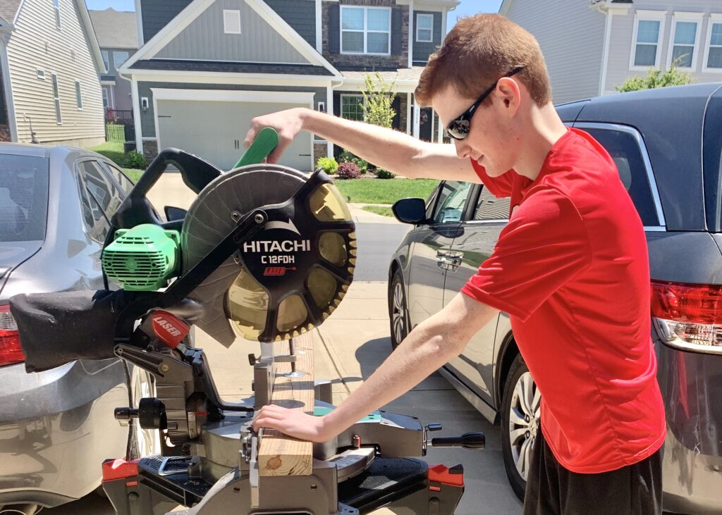 Teenage boy uses saw to cut wood. This summer is the perfect time to learn to safely use power tools. Create a corn hole set, build a raised bed garden or a new home for Fido. Look online for free build plans and what tools you will need.