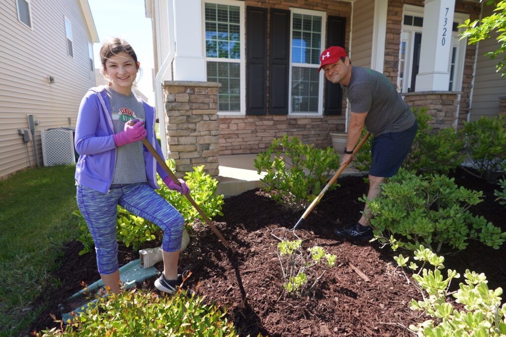 Father and daughter spread mulch in their lawn. Take the opportunity to tackle a big home improvement project together. Whether its adding a patio extension, landscaping your yard or finishing your basement think of ways to involve everyone in the family in the endeavor.