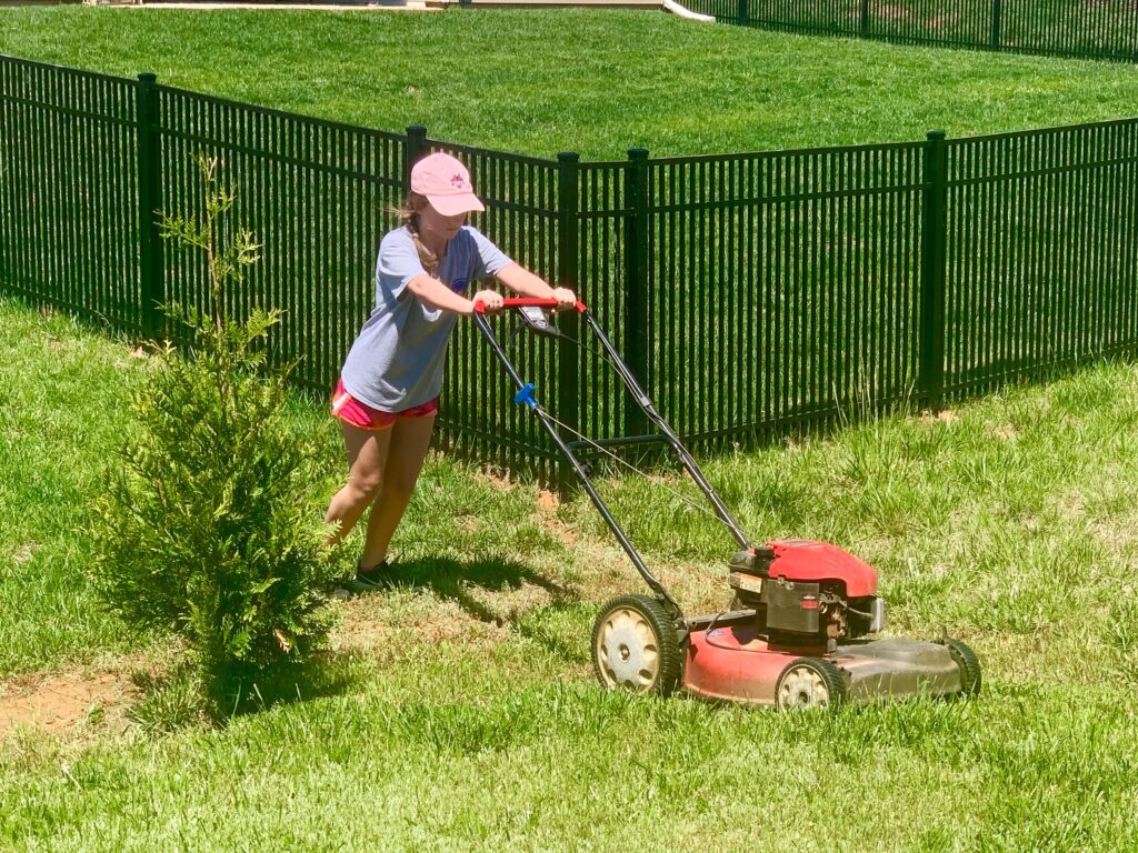 Girl mows lawn. Are your kids trying to earn some cash this summer while social distancing? Now may be the perfect time to train them on how to safely mow your lawn. This could be a new fun job for them and one less chore for you.
