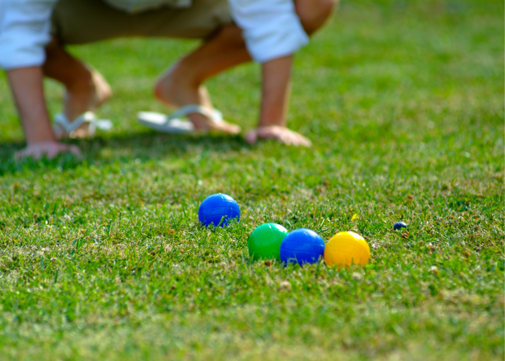 Clue-up photo of a game of Bocce Ball being played on a lawn. Invest in a croquet set, bocce ball set up, or badminton kit. Even an inexpensive frisbee can keep your family entertained for hours.