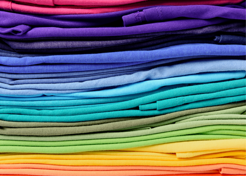 Colorful pile of folded clothing. It's the perfect time to organize the garage, declutter the attic, sort through daunting piles of paperwork or just go through those junk drawers. Donate any unwanted items to a local charity drop off site.
