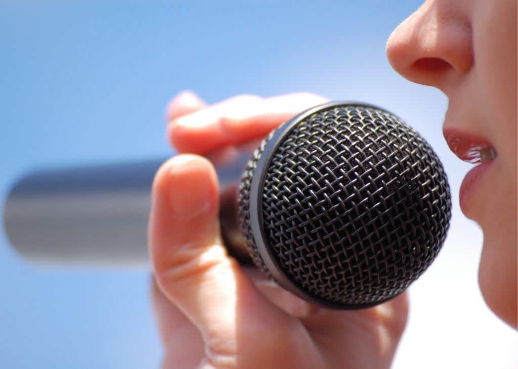 Close-up of girl singing into microphone. Check out the Disney Family Singalongs on Disney+ or make an Amazon playlist and singalong with the lyrics on your TV. Another fun option is to  sing some sweet harmonies with your very own karaoke machine.