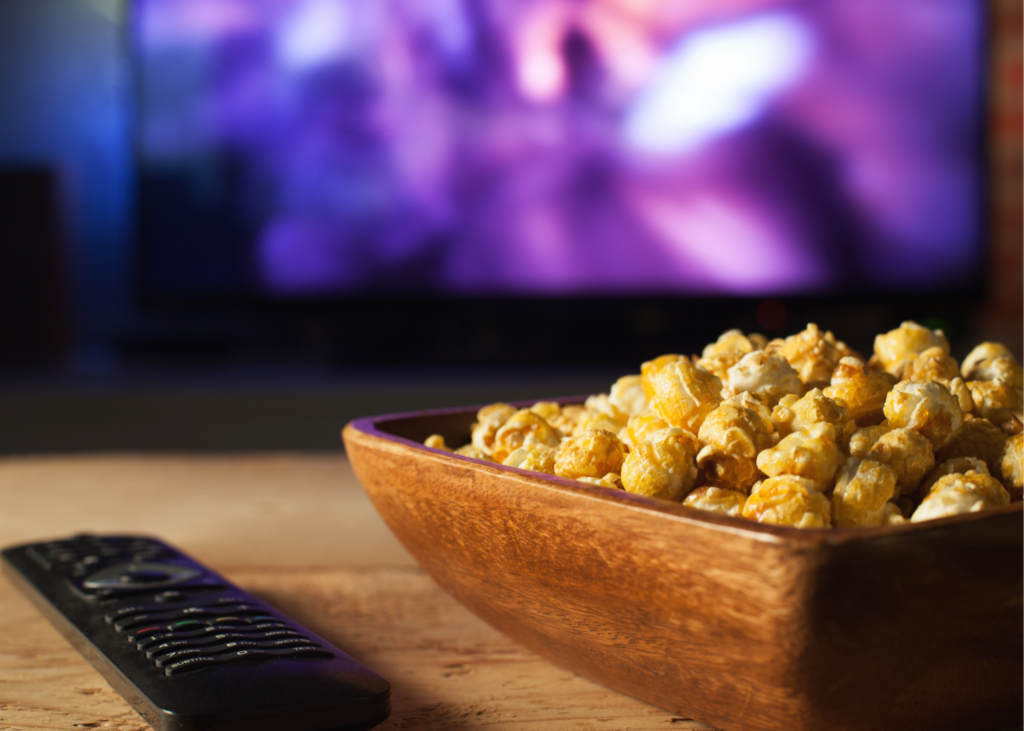 Bowl of popcorn and remote on coffee table with television in background. Take a walk down memory lane by watching old family home videos. Our kids love seeing themselves as toddlers and think it's hysterical how much we, as their parents have changed.