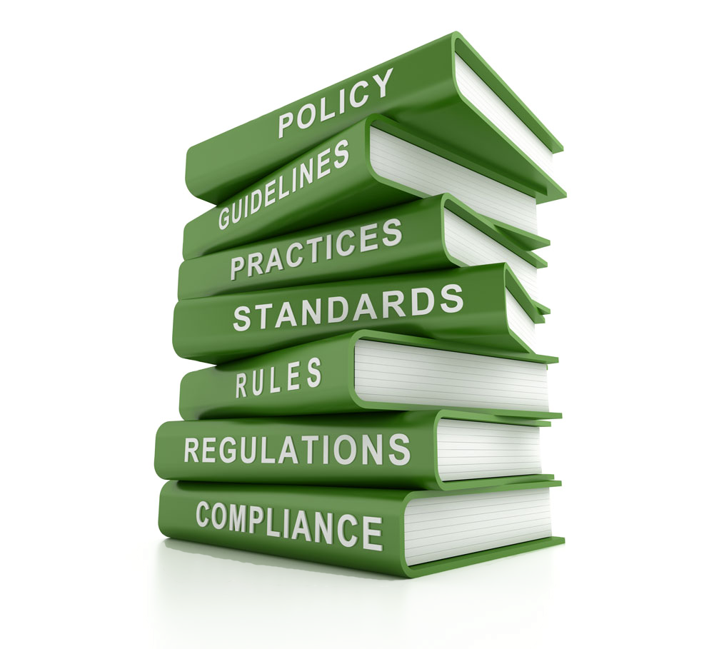 Green Books Staked with labels on the spine of compliance, regulations, rules, standards, practices, guidelines, and policy.