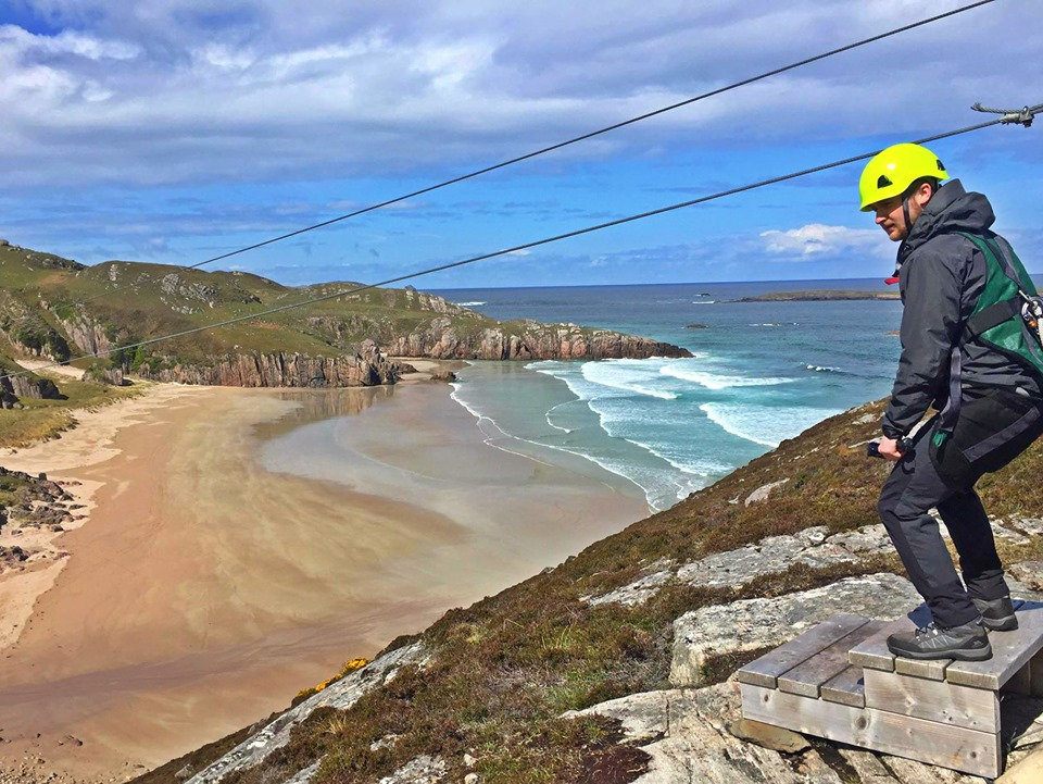 A man about to zip line over a beach in Scotland Gold Eagle Zip line