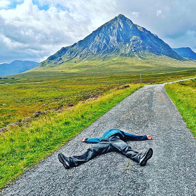 A man lying on the ground in front of the Glen Etive in Scotland