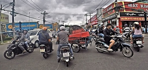 A large trailer being pulled by a scooter in Southeast Asia