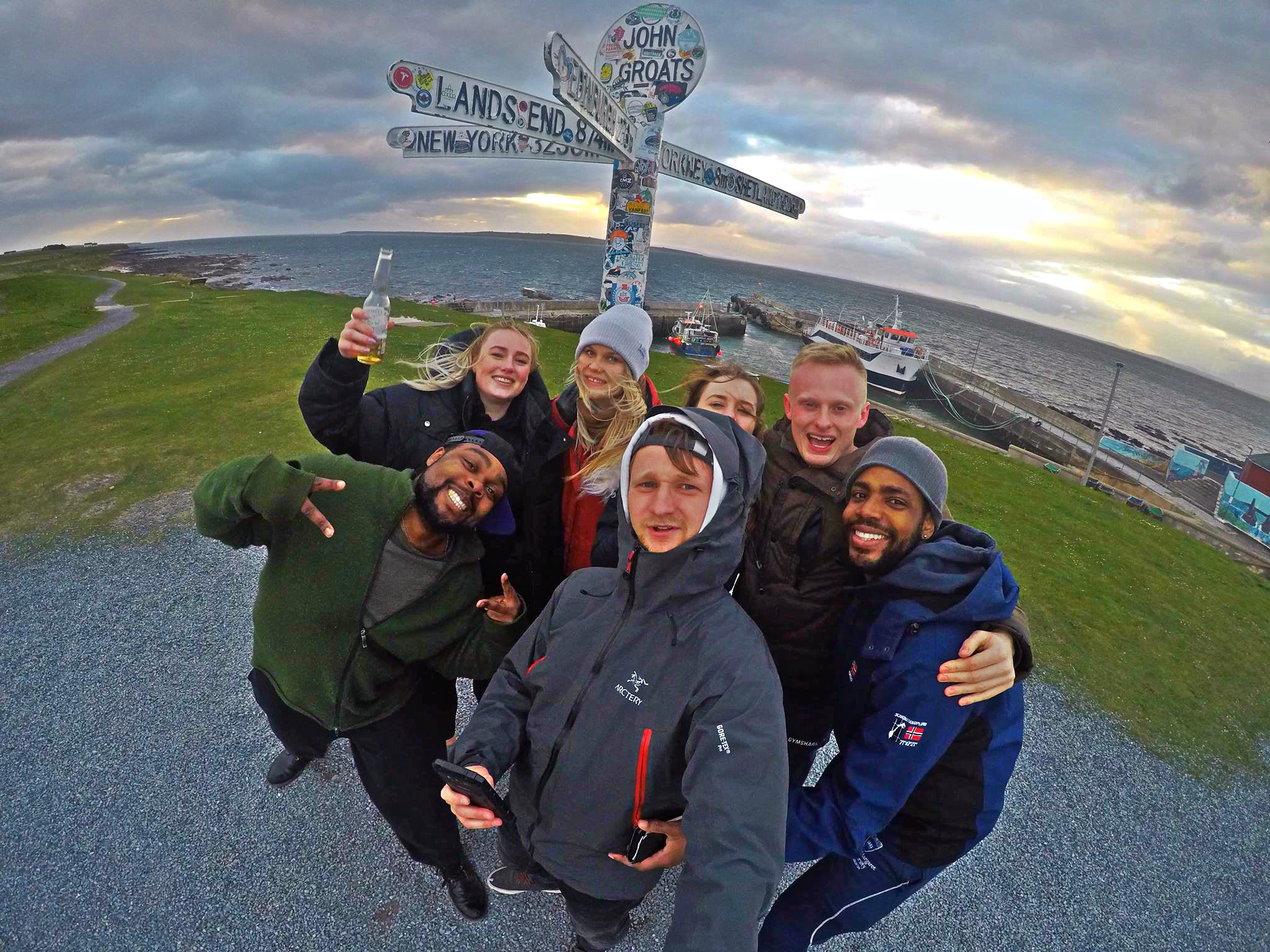 A group photo of happy people by John O Groats sign in Scotland