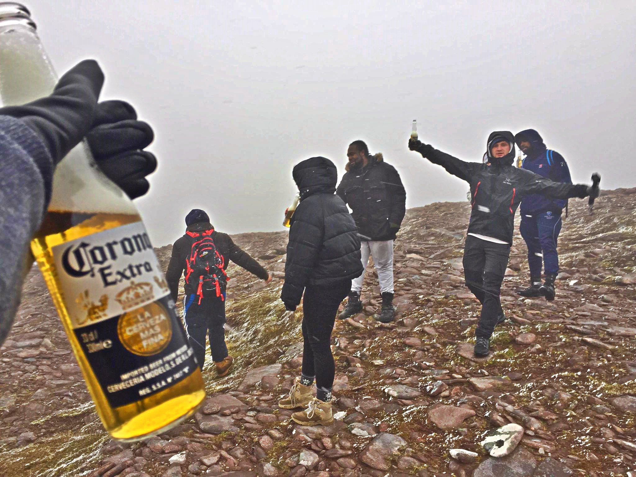 People drinking Corona extra beer on top of the mountain in snow