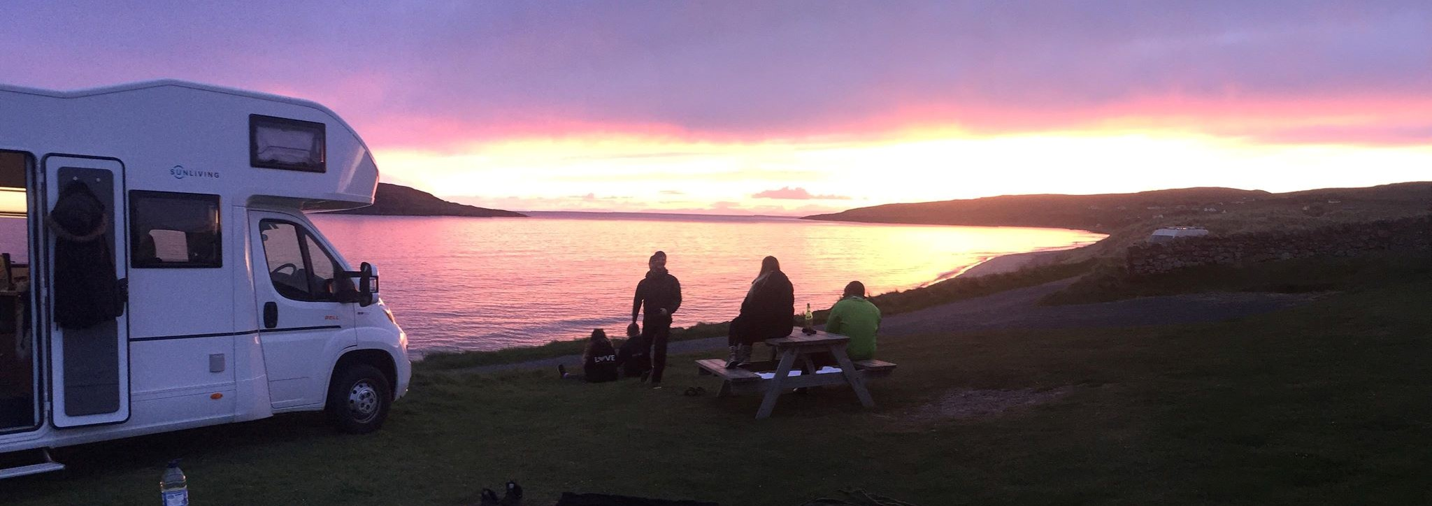 People watching a sunset on the beach next to a caravan in Scotland