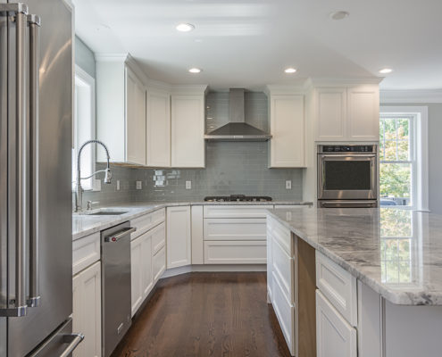 Kitchen area with white cabinets and quartz countertops