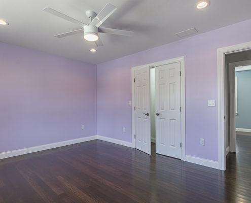 Designer bedroom with light purple walls, double doors and dark hardwood floors.