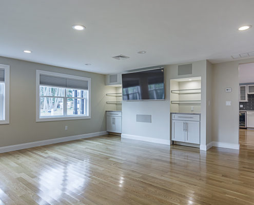Large hardwood floor living room area with large tv and great lighting