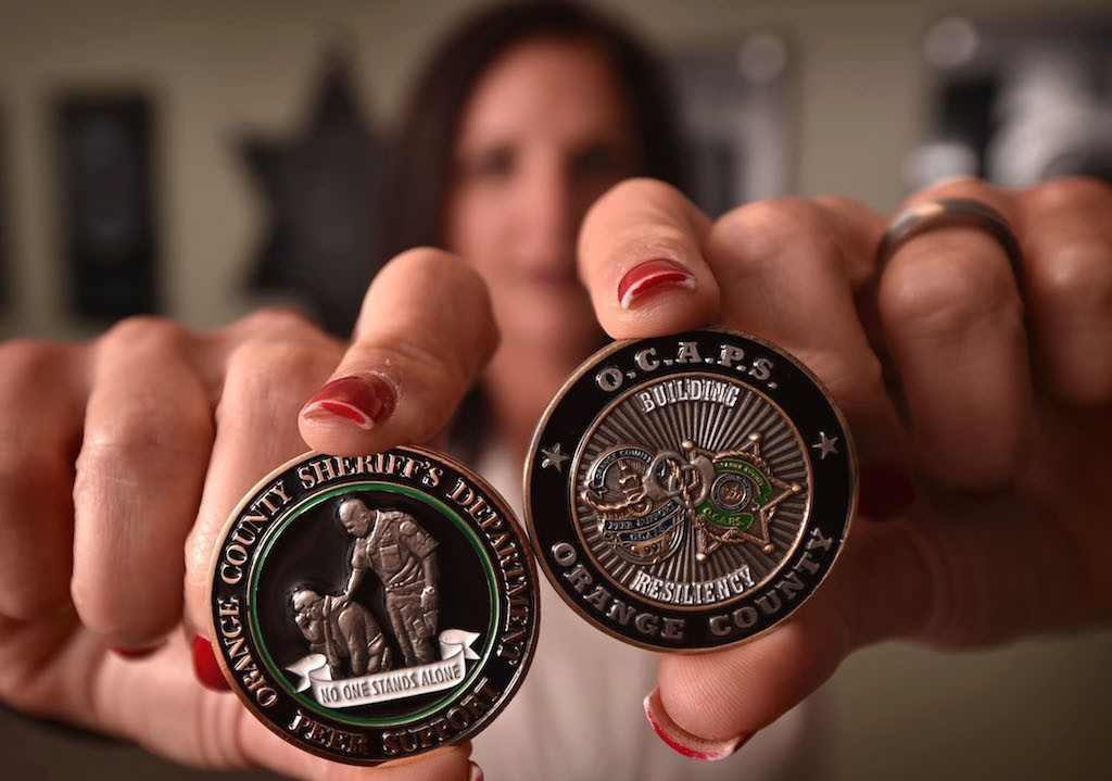 """Heather Williams, regional peer support coordinator for the Orange County Sheriff's Department, holds the Orange County Sheriff's Challenge Coin, left, for peer support particpants with the theme """"No One Stands Alone."""" On the right is the Orange County Association Of Peer Supporters, or OCAPS, coin. The graphic on the right represents, according to Dr. Williams, """"Law Enforcement of Orange County, intertwined and working together in the event that a department needs mutual aid or support in the aftermath of a critical incident."""" Photo by Steven Georges/Behind the Badge OC"""