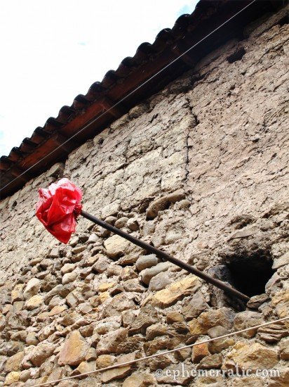 Red bag on a pole, the sign of chicha de jora nearby, Ollantaytambo, Peru