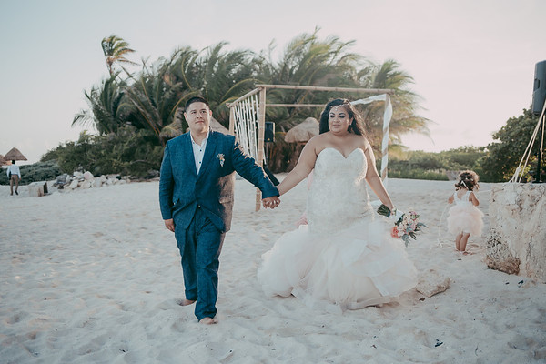curvy bride wearing dazzling plus size mermaid wedding gown holding groom's hand.