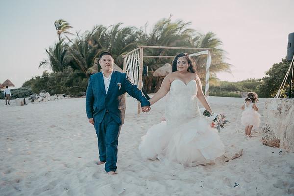 curvy bride wearing dazzling plus size mermaid wedding gown holding groom's hand.
