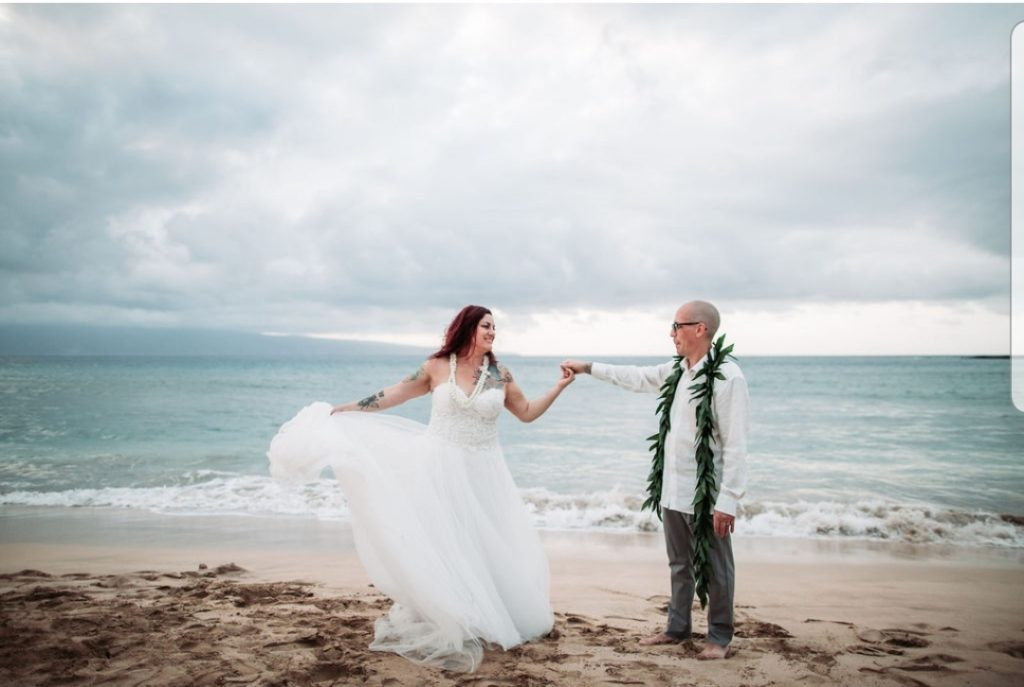 newlyweds twirling on the beach