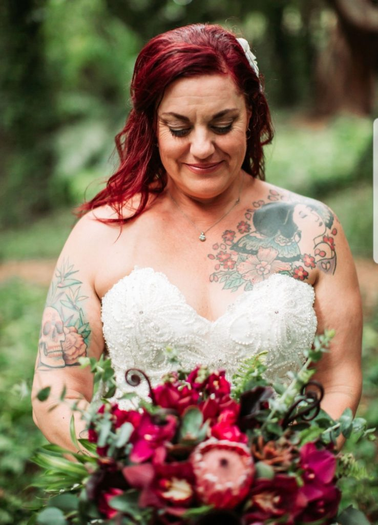 close up of plus size bride in gown holding flowers