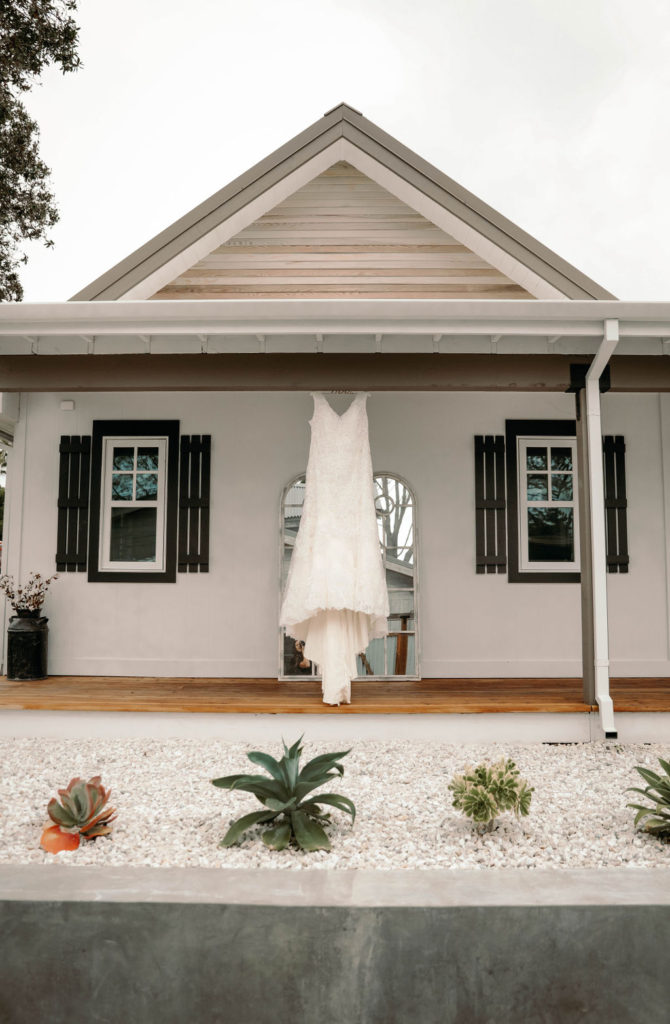plus size wedding dress hanging outside a house