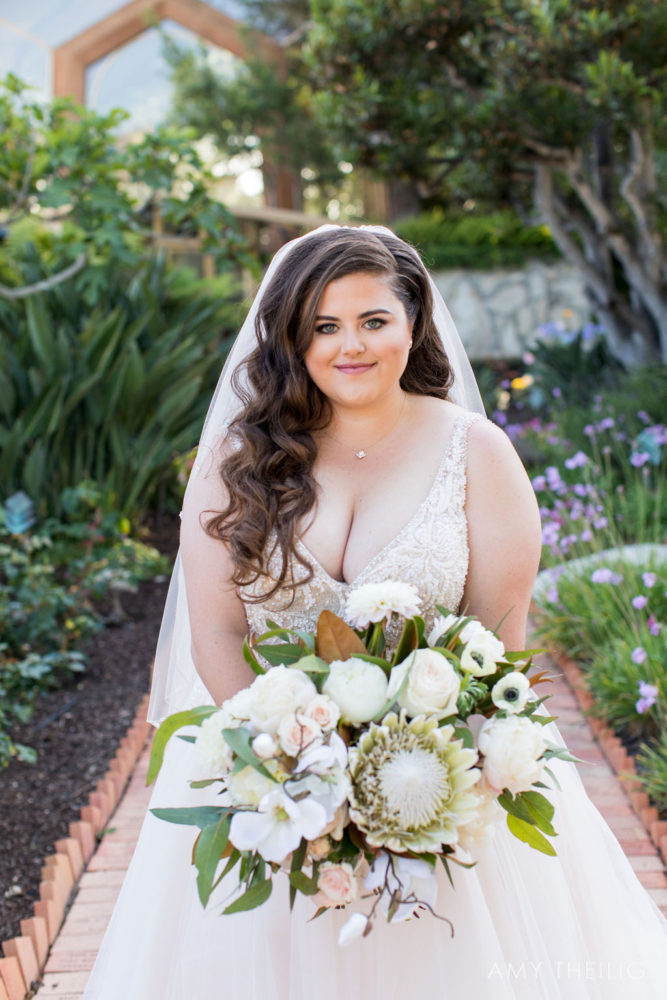 curvy-bride-holds-large-wedding-bouquet-with-mixed-flowers