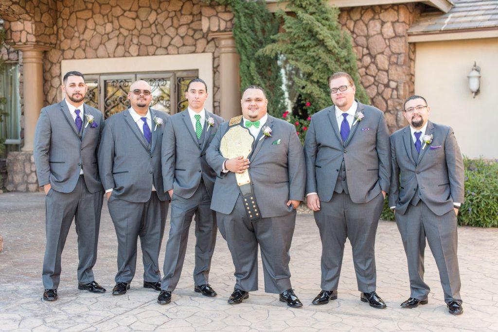 groom wears wrestling belt with groomsmen in suits