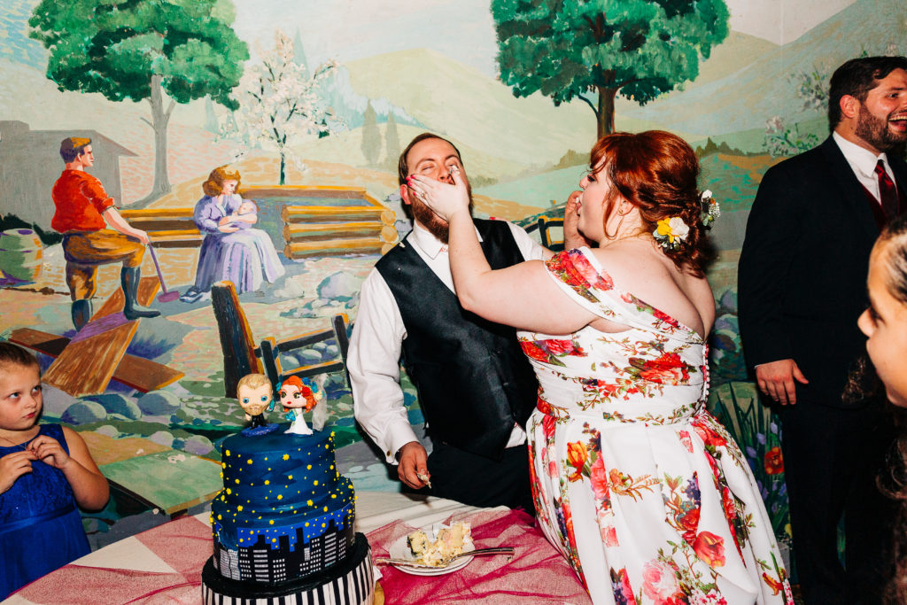 newlywed couple smashing cake in their faces