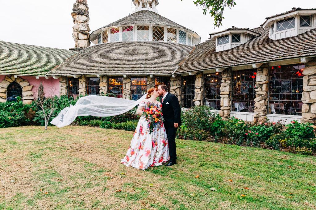 bride-wearing-floral-wedding-dress-and-groom-kissing-madonna-inn-california
