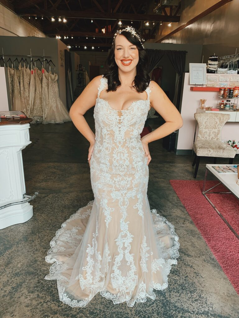 Smiling bride in two toned mermaid wedding dress with lace pattern and lace edged train