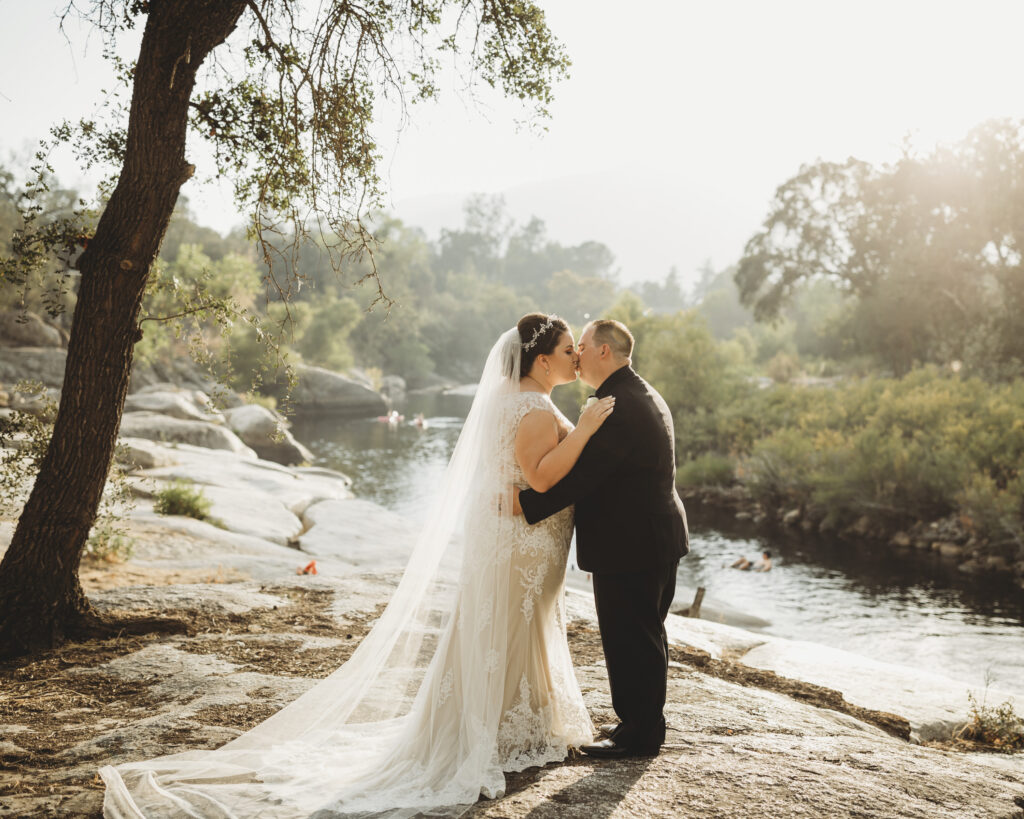 Kissing couple on their wedding day by river in nature with rocks, lace wedding dress, black tux, cathedral length plain veil