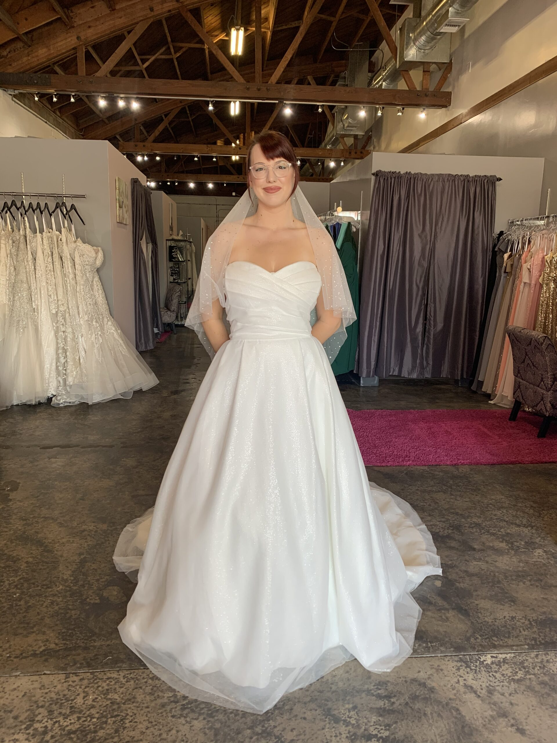 Sweetheart neckline ruched bodice sparkle tulle ballgown with sparkle moon and sun veil on tall geeky model with glasses in Longbeach California