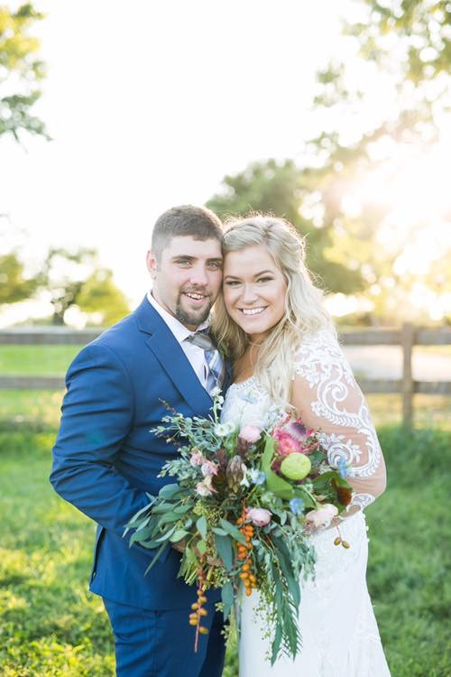 Smiling couple on wedding day with rustic bouquet with embroidered long sleeve gown and navy tuxedo