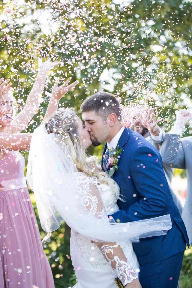 Kissing couple on wedding day flower petals