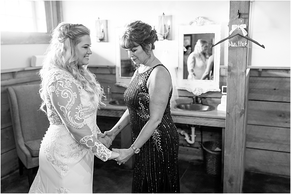 Mom and daughter in embroidered long sleeve wedding mermaid gown praying before wedding ceremony