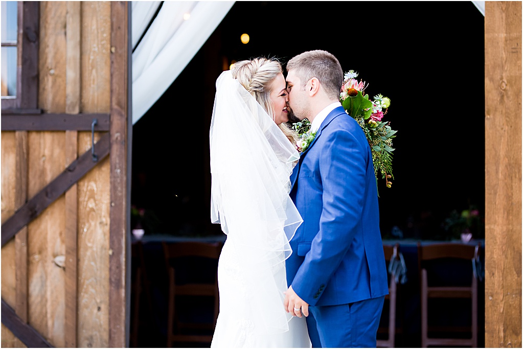 Smiling bride on wedding day with long veil kissing husband in navy tux in rustic barn