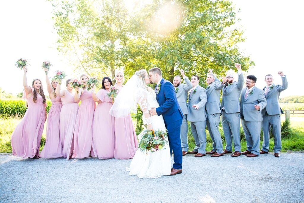 Rustic wedding day couple bridesmaids & groomsmen cheering wedding couple kiss