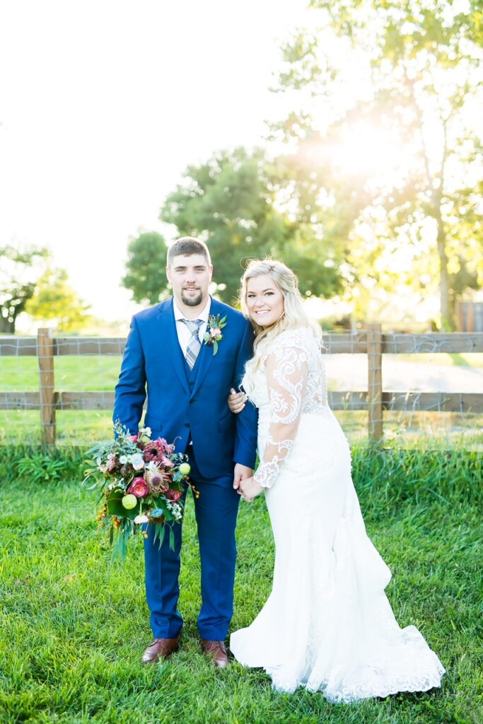 Smiling couple on wedding day in grass rustic location white long sleeve dress navy tux