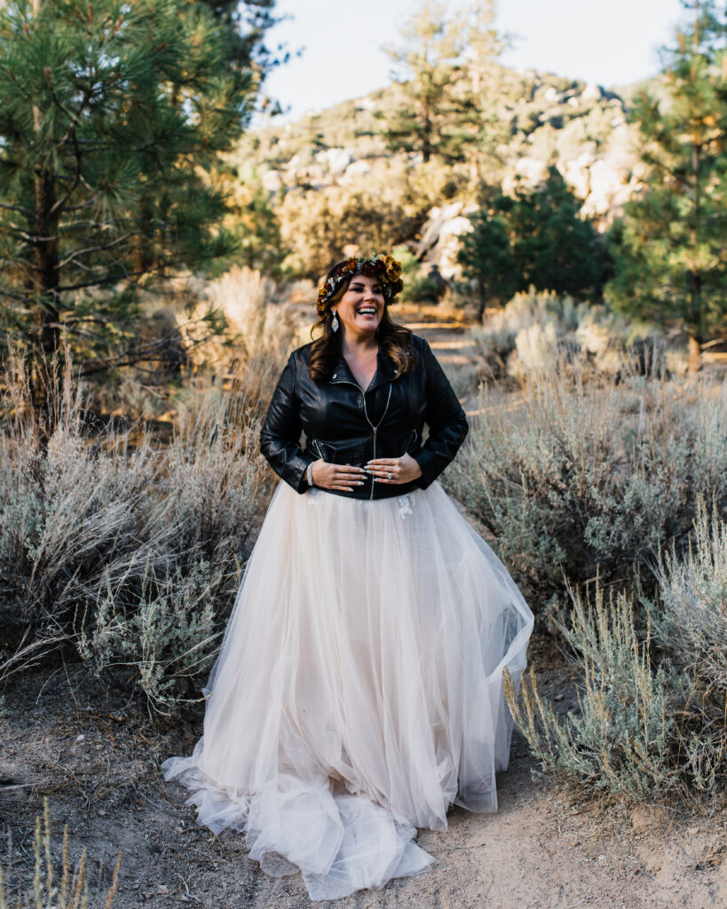 Smiling bride in champange tulle skirt wedding dress with rustic flower crown and black leather jacket