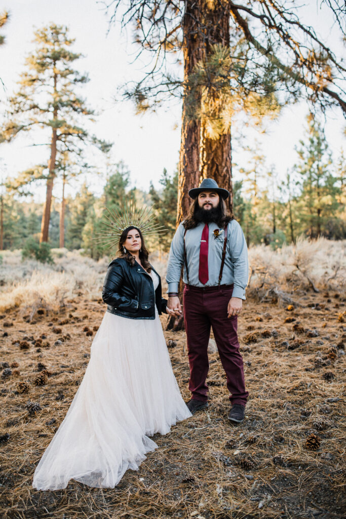 Boho bride and groom rustic elopement champange tulle skirt with black leather jacket and gold crown groom in maroon pants and red tie