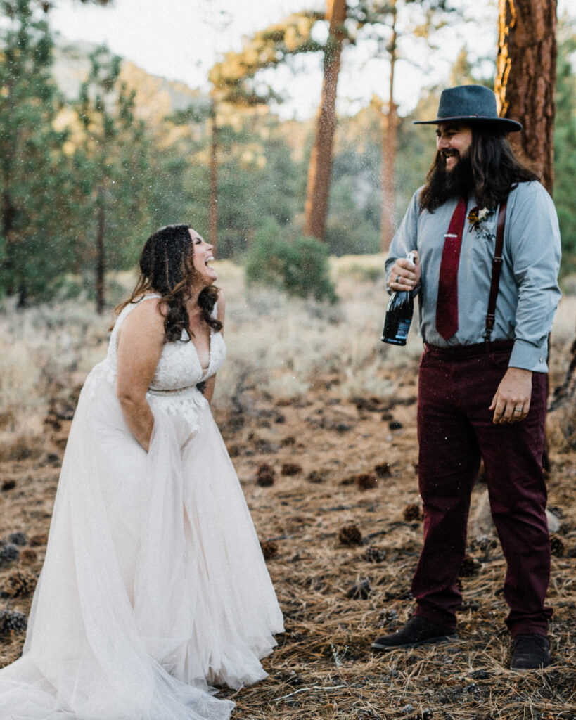 Happy smiling couple popping champagne in forest