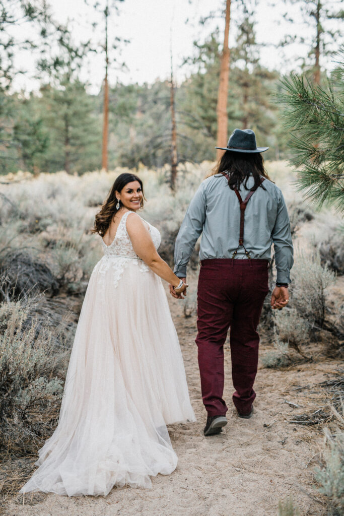 Bride smiling back at camera walking with groom in desert elopement