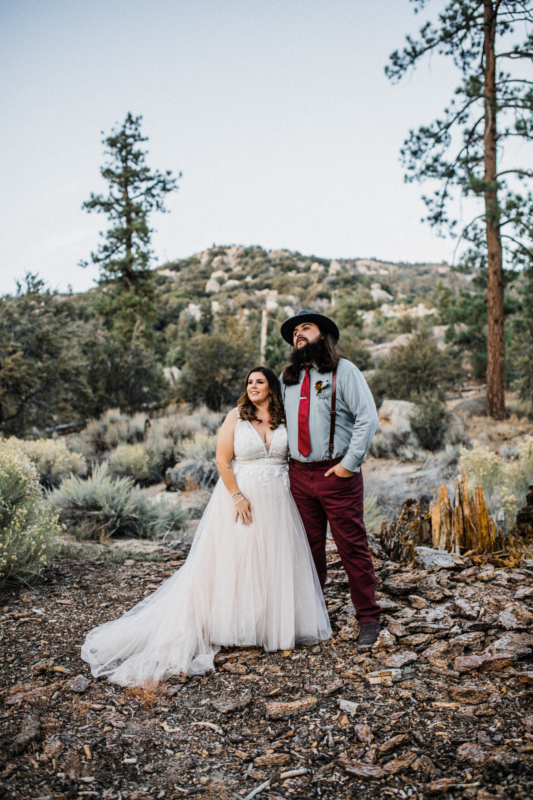 Smiling couple in forest elopement with champagne a-line style dress