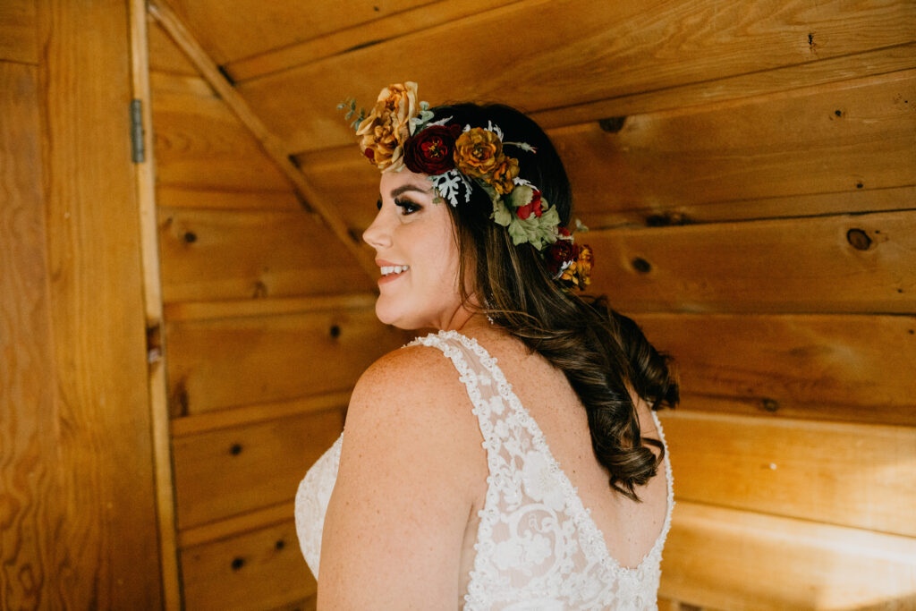Smiling plus size bride with rustic rose flower crown and ivory embroidered top