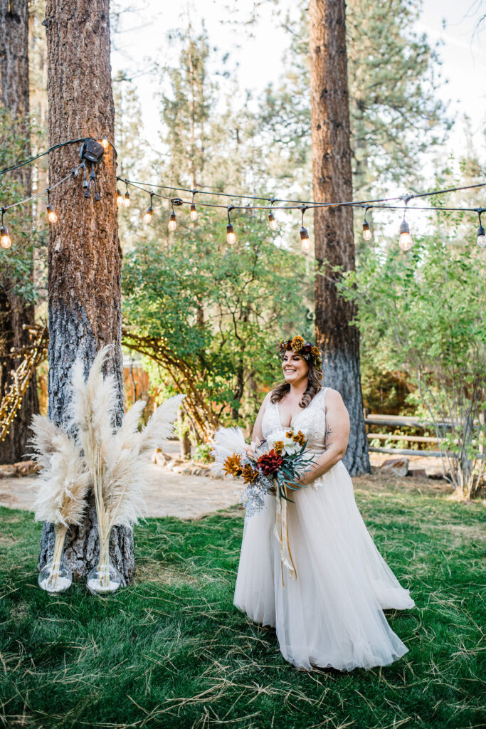 Beautiful boho bride on wedding day in forest with rustic flower crown and boho bouquet